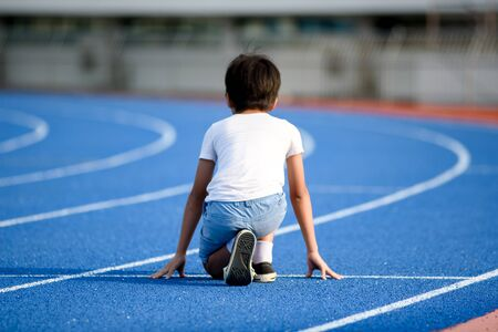 Foto per Young Asian boy prepare to start to run on a blue track in summer day - Immagine Royalty Free