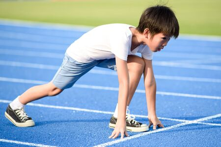 Foto de Young Asian boy prepare to start run on a blue track in summer day - Imagen libre de derechos