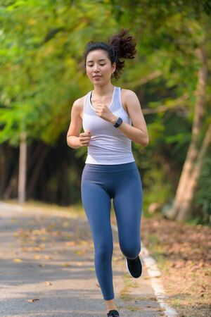 Foto de Selective focus at young Asian woman running with happy in a park during summer day in a morning. - Imagen libre de derechos