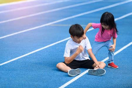 Foto de Young boy and girl play on a bluetrack after running in summer - Imagen libre de derechos