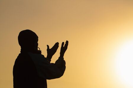 Photo pour Man praying at sunset mountains raised hands Travel Lifestyle spiritual relaxation emotional concept, Freedom and travel adventure. - image libre de droit