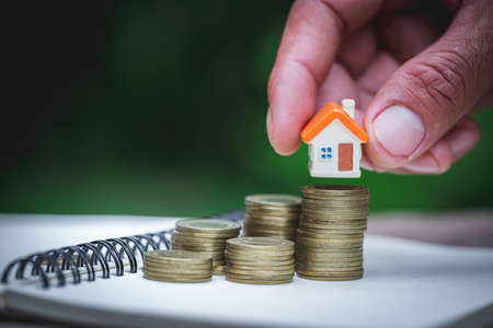 Photo pour Woman's hand putting house model on coins stack. Concept for property ladder, planning savings money of coins to buy a home concept property mortgage and investment for a house. - image libre de droit