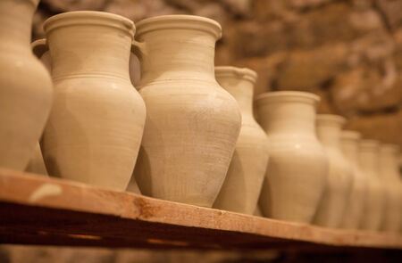 Pottery dishes on shelves in pottery workshop
