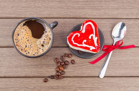 Valentine`s day dessert, black coffee, heart cake and red rose on wooden table