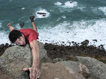 adventure rock climbing man dangling from a cliff