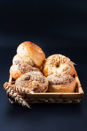 Foto für Food bakery concept Homemade organic bagels in bamboo wicker tray on black background - Lizenzfreies Bild