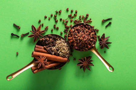 Photo pour Food spices concept Organic Chinese five spice, cinnamon sticks, star anise, fennel seeds, Sichuan peppercorn and cloves in a copper cup on green background with copy space - image libre de droit