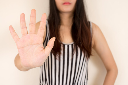 young woman showing her denial with NO on her hand.