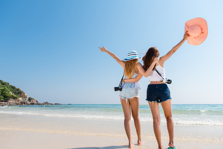 Foto de Portrait of two young asian female friends walking on the sea shore turn back at camera laughing. Multiracial young women strolling along a beach. - Imagen libre de derechos