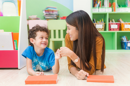 Foto de Young asian woman teacher teaching american kid in kindergarten classroom with happiness and relaxation. Education, elementary school, learning and people concept - teacher help school kids classroom. - Imagen libre de derechos