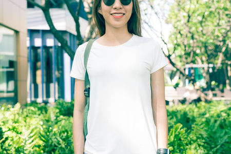 Asian hipster girl long brown hair in white blank t-shirt is standing in the middle of street. A female in street wear is standing on a green urban background. Empty mock up space for text or design.