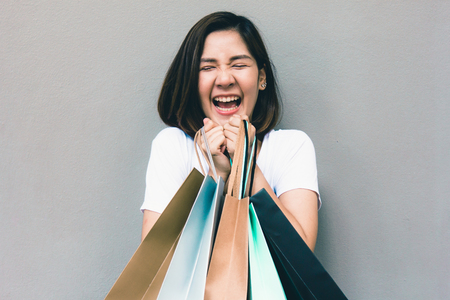 Foto de Young happy summer shopping asian woman with shopping bags on grey background at copy space - Imagen libre de derechos