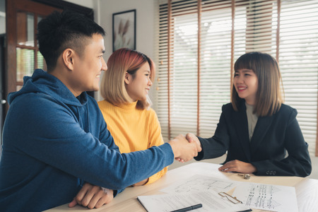 Photo pour Happy young Asian couple and realtor agent. Cheerful young man signing some documents and handshaking with broker while sitting at desk. Signing good condition contract. - image libre de droit