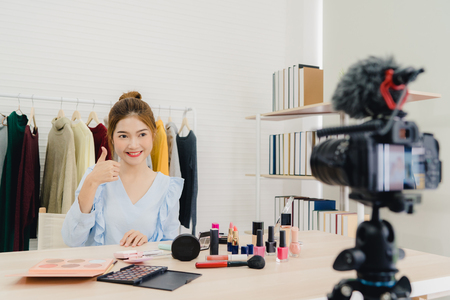 Photo pour Beauty blogger present beauty cosmetics sitting in front camera for recording video. Beautiful asian woman use cosmetics while review make up tutorial broadcast live video to social network by internet. - image libre de droit
