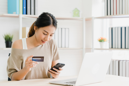 Photo pour Beautiful Asian woman using smartphone buying online shopping by credit card while wear sweater sitting on desk in living room at home. Lifestyle woman at home concept. - image libre de droit