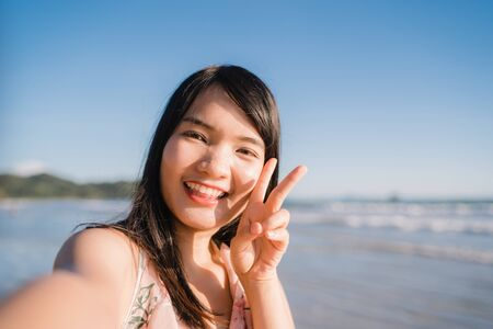 Photo for Tourist Asian woman selfie on beach, young beautiful female happy smiling using mobile phone taking selfie on beach near sea when sunset in evening. Lifestyle women travel on beach concept. - Royalty Free Image