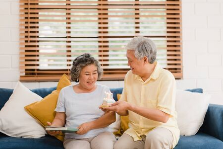 Photo pour Asian elderly couple man holding cake celebrating wife's birthday in living room at home. Japanese couple enjoy love moment together at home. Lifestyle senior family at home concept. - image libre de droit