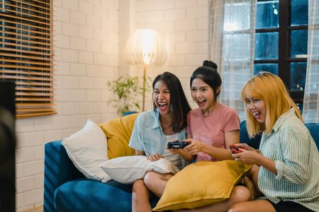 Photo pour Group of Asian women couple play games at home, female using joystick having funny moment together on sofa in living room in night. Teenager young friend football fan, celebrate holiday concept. - image libre de droit