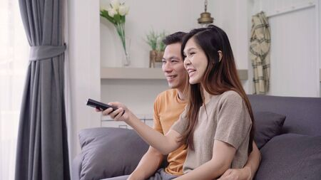 Asian couple watching TV and drinking warm cup of coffee in living room at home, sweet couple enjoy love moment while lying on the sofa when relax at home. Lifestyle couple relax at home concept.
