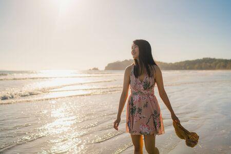 Foto de Young Asian woman walking on beach. Beautiful female happy relax walking on beach near sea when sunset in evening. Lifestyle women travel on beach concept. - Imagen libre de derechos