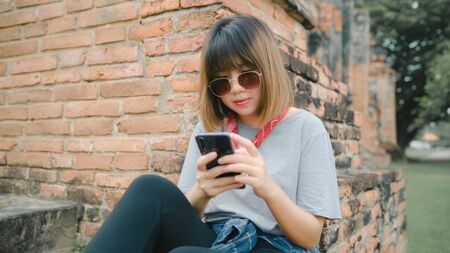Photo pour Traveler Asian woman using smartphone checking social media while relax after spending holiday trip at Ayutthaya, Thailand, female enjoy her journey at amazing landmark in traditional city. - image libre de droit