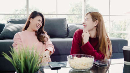 Photo pour Asian women using smartphone and eating popcorn in living room at home, group of roommate friend enjoy funny moment while lying on the sofa. Lifestyle women relax at home concept. - image libre de droit
