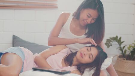 Photo pour Asian Lesbian lgbtq women couple kiss and hug on bed at home. Young Asia lover female happy relax rest together spend romantic time after wake up in bedroom at home in the morning concept. - image libre de droit