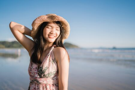 Photo for Young Asian woman feeling happy on beach, beautiful female happy relax smiling fun on beach near sea when sunset in evening. Lifestyle women travel on beach concept. - Royalty Free Image