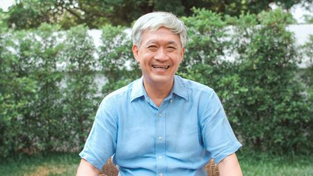 Photo for Portrait Asian Chinese senior man feeling happy smiling at home. Older male relax toothy smile looking to camera while lying in the garden at home in the morning concept. - Royalty Free Image