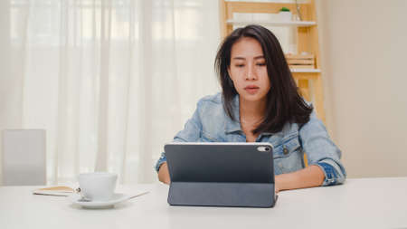 Photo pour Frustrated Young Asia lady having problem with not working tablet computer sitting on desk. Freelance smart business women casual wear using tablet working in workplace in living room at home office. - image libre de droit