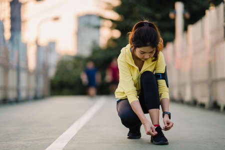 Photo pour Beautiful young Asia athlete lady exercises tying laces for work out in urban environment. Japanese teen girl wearing sport clothes on walkway bridge in early morning. Lifestyle active sporty in city. - image libre de droit