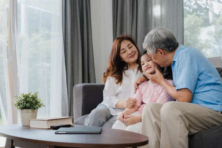 Photo pour Asian grandparents kiss granddaughter cheek at home. Senior Chinese, old generation, grandfather and grandmother using family time relax with young girl kid lying on sofa in living room concept. - image libre de droit