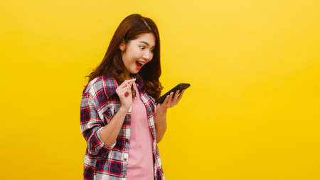 Photo pour Portrait of surprised Asian female using mobile phone with positive expression, dressed in casual clothing and looking at camera over yellow background. Happy adorable glad woman rejoices success. - image libre de droit