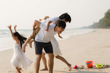 Photo pour Asian young happy family enjoy vacation on beach in the evening. Dad, mom and kid relax playing together near sea when sunset while travel holiday. Lifestyle travel holiday vacation summer concept. - image libre de droit