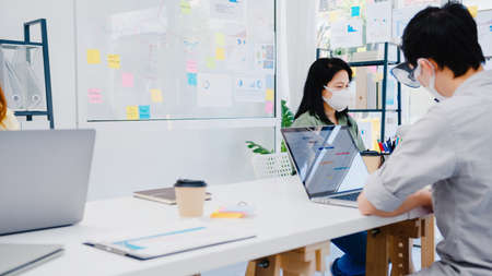 Foto de Asia businesspeople entrepreneur wearing medical face mask for social distancing in new normal situation for virus prevention while using laptop back at work in office. Lifestyle after corona virus. - Imagen libre de derechos