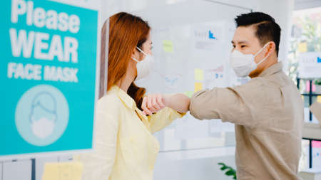 Photo pour Asia businesspeople greeting with elbow bump and wear medical face mask for social distancing in new normal situation for virus prevention back at work in office. Lifestyle and work after coronavirus. - image libre de droit