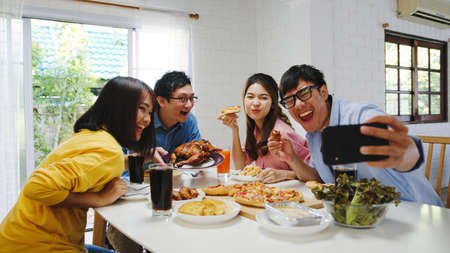 Photo pour Happy young group having lunch at home. Asia family party eating pizza food and making selfie with her friends at birthday party at dining table together at house. Celebration holiday and togetherness - image libre de droit