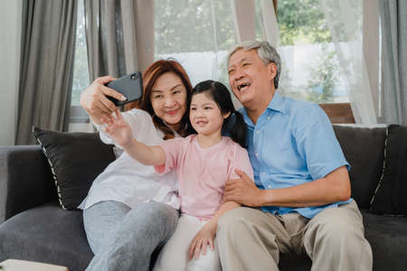 Photo pour Asian grandparents selfie with granddaughter at home. Senior Chinese, grandpa and grandma happy spend family time relax using mobile phone with young girl kid lying on sofa in living room concept. - image libre de droit