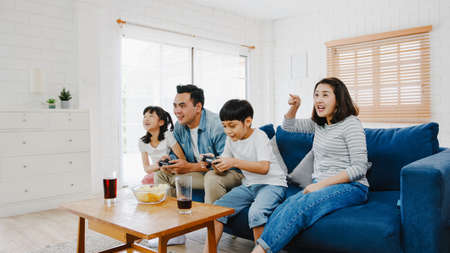 Foto de Happy Asia family dad, mom and kids funny playing video game with technology console in living room at house. Self-isolation, stay at home, social distancing, quarantine for coronavirus prevention. - Imagen libre de derechos