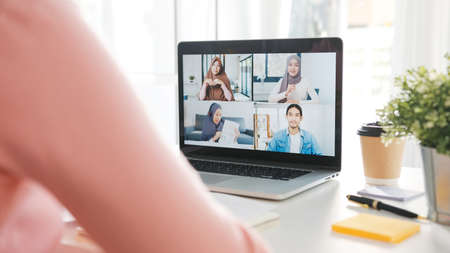Foto de Young Asia businesswoman using laptop talk to colleague about plan in video call meeting while work from home at living room. Self-isolation, social distancing, quarantine for corona virus prevention. - Imagen libre de derechos