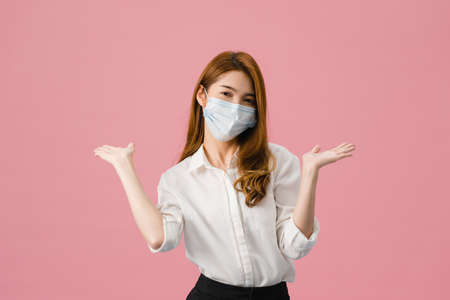 Photo pour Young Asia girl wearing medical face mask showing peace sign, encourage with dressed in casual cloth and looking at camera isolated on pink background. Social distancing, quarantine for corona virus. - image libre de droit