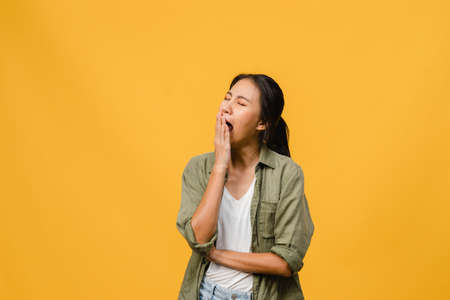 Photo for Portrait of Young Asia lady with negative expression, bored yawning tired covering mouth with hand in casual clothing isolated on yellow background with blank copy space. Facial expression concept - Royalty Free Image