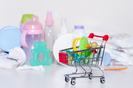 Photo pour Shopping cart with baby pacifiers with things for baby: purchase for a newborn concept - image libre de droit