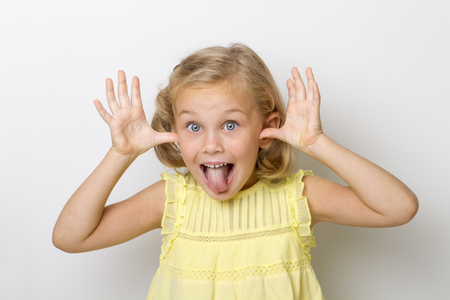 Photo pour Head and hands shot of Little girl sticking out her tongue at the camera for fun - image libre de droit