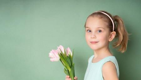 Foto de Adorable smiling little girl with tulips over green spring background - Imagen libre de derechos