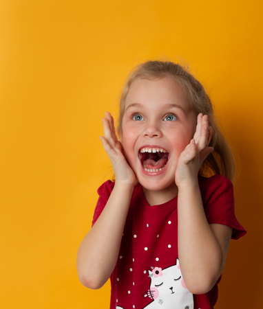 Photo pour Image of excited screaming cute little standing isolated over yellow background. Looking away camera. - image libre de droit