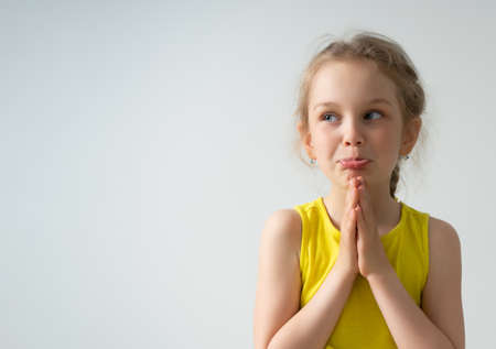 Photo for cute preschooler girl begs to buy or give her something, clasped her hands and stretched out her lower lip. Children, gestures and emotions. Cropped shot isolated on white, copy space. - Royalty Free Image