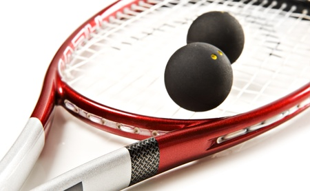 Close up of a red and silver squash racket and ball on a white background with space for text