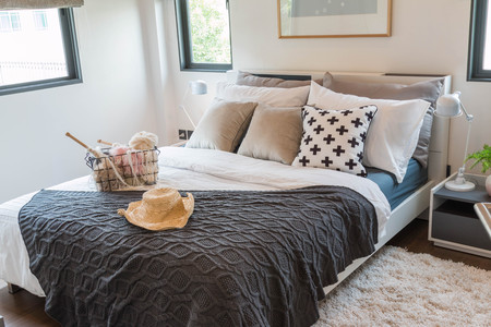 Multiple pillows and hat on a white bed in a warm bedroom.
