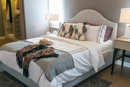 Women's hats and many pillow on the bed in warm bedroom